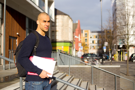 textbooks: young man holding textbooks and a rucksack