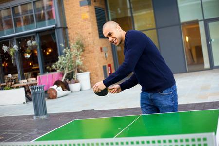 pong: young man playing ping pong