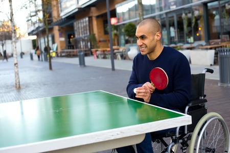 jugando tenis: hombre joven en una mesa de tenis de ruedas jugando