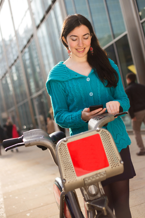 boris: young woman with a hire bike checking her phone