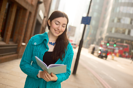 textbook: young woman reading a textbook in the street