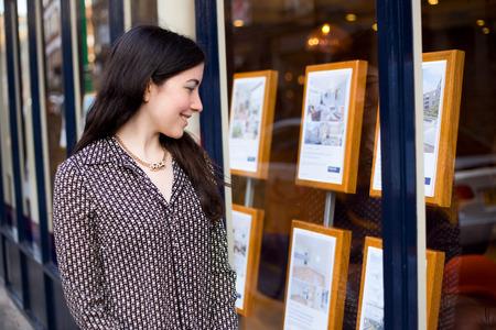 mujer joven mirando en la ventana de un agente inmobiliario
