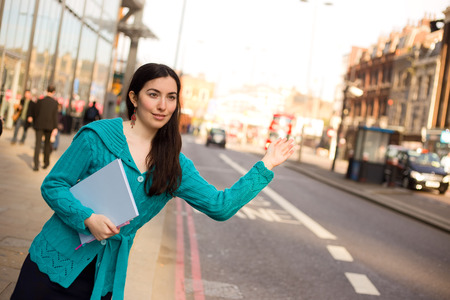 hailing: young woman hailing a taxi in the street Stock Photo
