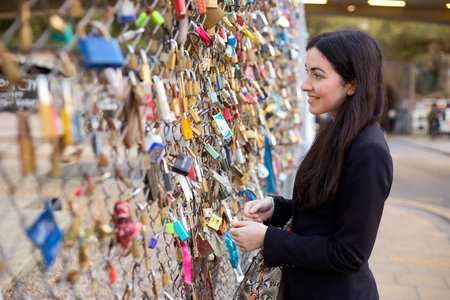 padlocked: girl looking at love locks attached to a fence