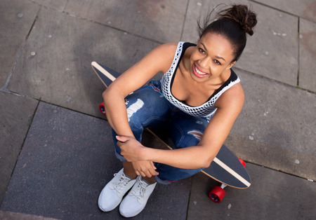 womna: young womna sitting on her skateboard Stock Photo