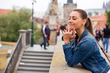 young woman looking at the view from charles bridge, prague