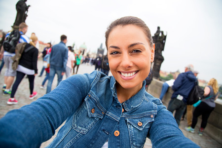 charles bridge: young woman taking a selfie on charles bridge in Prague