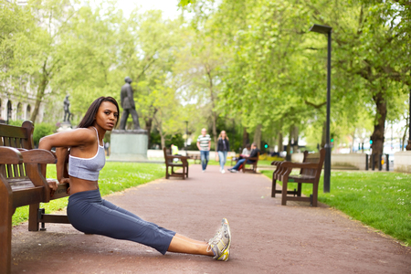 tricep: young woman doing tricep dips in the park Stock Photo