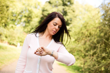 timekeeping: young woman walking through the park checking the time