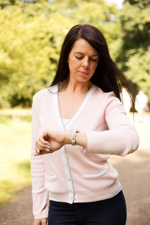 timekeeping: young woman walking in the park checking her watch