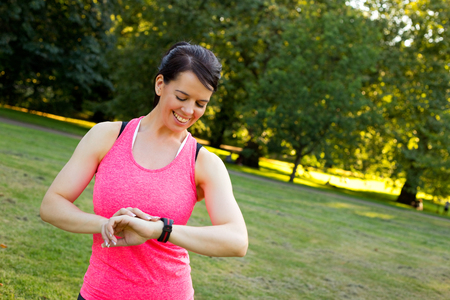 young woman checking her fitness monitor in the park Stock Photo
