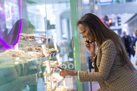 Young woman looking in a cake shop window Stock Photo