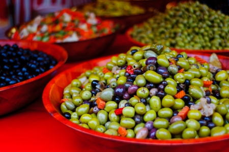 Green and black olives compasition in a red bowl Stock Photo