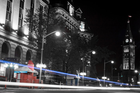 Traffic passes on busy street in front of Parliament Hill in Ottawa at night. photo