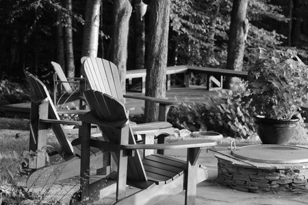 Adirondack chairs set around a deck against a wooded background. photo
