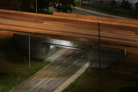 Blurred motion of cars passing on highway overpass and busy street underneath at night.