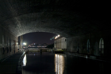 The Ottawa Locks between the Rideau Canal and the Ottawa River from under a bridge at night. The Alexandra Bridge between Ottawa, Ontario and Gatineau, Quebec can be seen in the background.