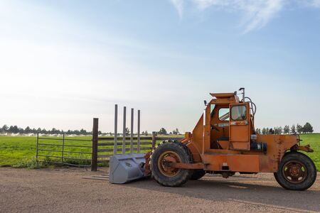 Side angle of orange tractor with a plow in a field with blue sky in the background