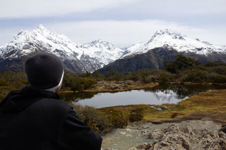 Milford Sound Summit Trek Man looking at a beautiful view of mountains at summit