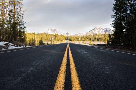 Líneas amarillas en la calzada que conduce hacia las montañas Foto de archivo