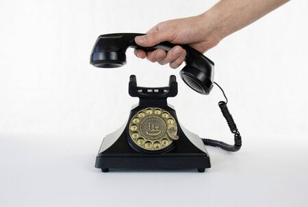 Isolated picking up the phone black rotary telephone white isolated background 免版税图像