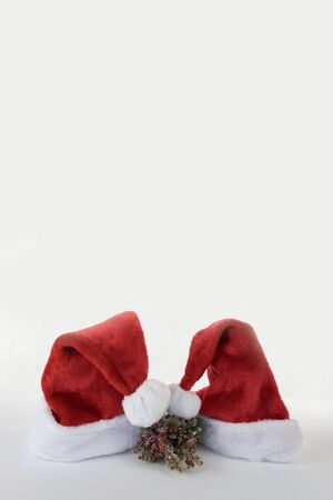 Vertical Santa and mrs Claus red hat kissing on white background copy space