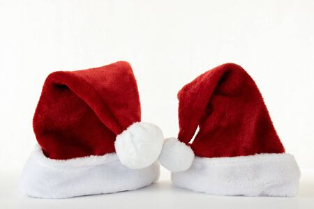 Santa and mrs Claus red hat kissing on white background copyspace