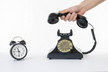 Rotary telephone on white isolated background with clock time to call