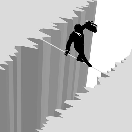 risky: A business man takes a risky dangerous walk on a tightrope over a cliff drop off to safety.