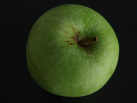 Close up of a granny smith apple on black background