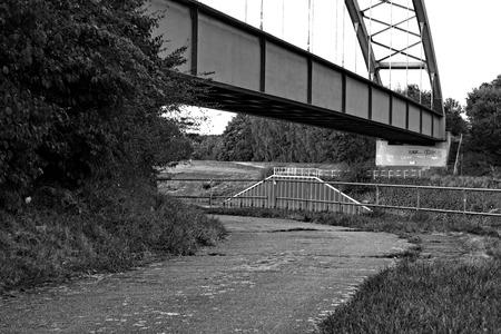 An old asphalt road runs under a railway bridge
