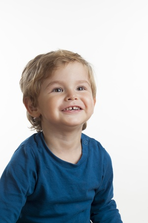 Series of close up portraits of a toddle with different expressions.  Studio shot on white background.