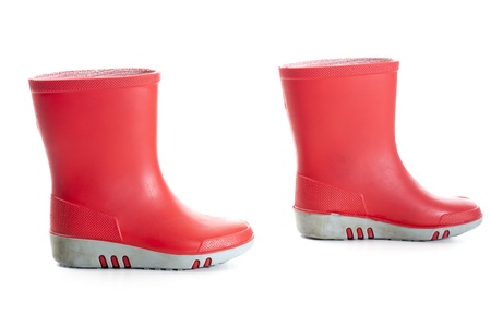 Pair of red wellies in kids size, one step apart.  Studio shot, isolated on white background.