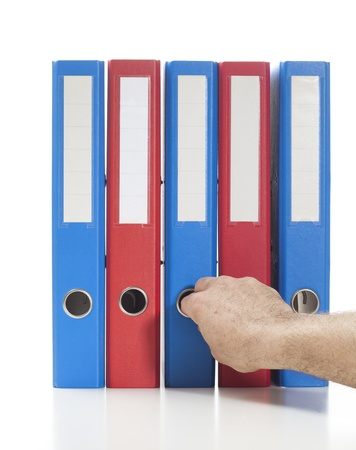 Set of binders in red and blue colors. Single hand pulling one of the binders  Studio shot, isolated on white. Stock Photo
