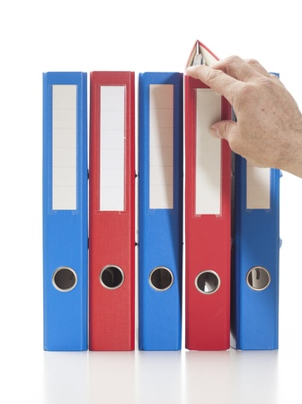 Set of binders in red and blue colors. Single hand pulling one of the bindersStudio shot, isolated on white. Stock Photo - 17669615