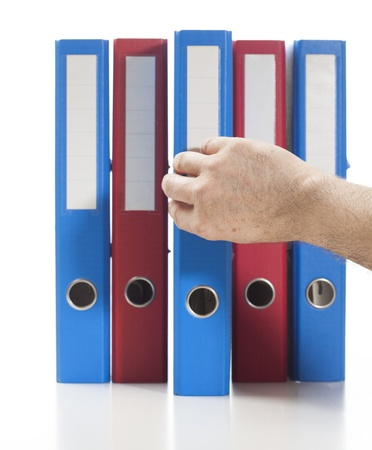 Set of binders in red and blue colors. Single hand pulling one of the bindersStudio shot, isolated on white. Stock Photo - 17656055
