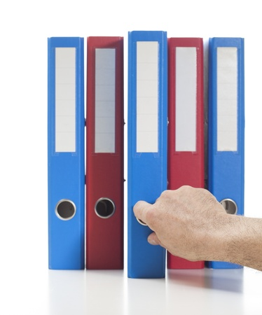 Set of binders in red and blue colors. Single hand pulling one of the bindersStudio shot, isolated on white. Stock Photo - 17656017
