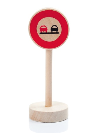 Wooden traffic sign restricting overtaking, isolated on white with reflection on the stand.  Toy made from wood with minor blemishes - please zoom in closely if you are in doubt if it suits your project needs..