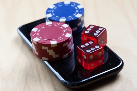 Concept shot with poker chips on a mobile phone and dices - online gambling, mobile gaming etc. Stock Photo