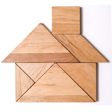 brainteaser: House built from pieces of a traditional Japanese and Chinese Puzzle Game made of different wood parts. Stock Photo