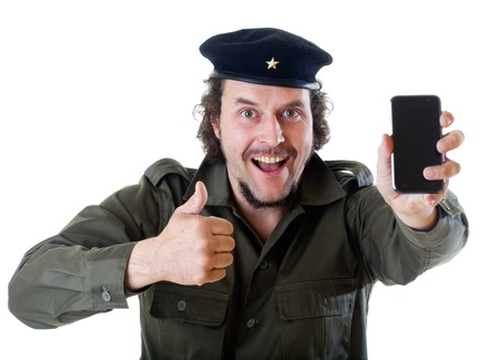 guerilla warfare: Mid-aged man in authentic 1950s60s military uniform shirt and beret hat, holding a modern smart phone and showing thumbs up.  Shot in studio on white background..