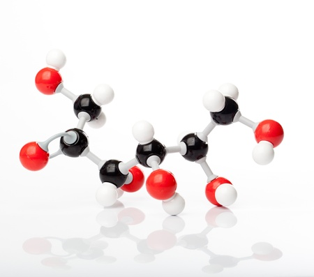 fructose: Molecule of fructose or fruit sugar, molecular formula C6H14O6. Carbon represented by the black balls, oxygen by a red ball, Hydrogen by the white balls attached to the carbon or oxygen.  Shot with reflection on the ground.. Stock Photo