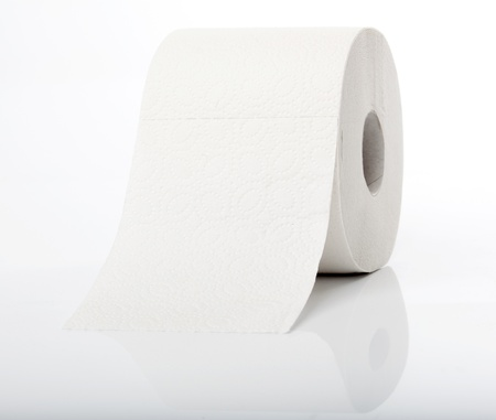 Simple roll of no name toilet paper.  Shot on studio on reflecting ground. Stock Photo
