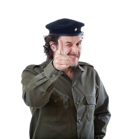 guerilla warfare: Mid-aged man in authentic 1950s60s military uniform shirt and beret hat, aiming with his hand into the camera.  Shot in studio on white background.. Stock Photo