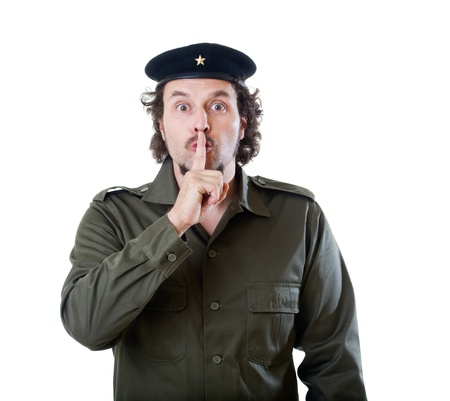 guerilla warfare: Mid-aged man in authentic 1950s60s military uniform shirt and beret hat, putting his finger in front of his mouth.  Shot in studio on white background..