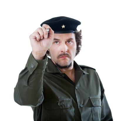 guerilla warfare: Mid-aged man in authentic 1950s60s military uniform shirt and beret hat, holding a pen in his hands, writing on the front.  Shot in studio on white background.. Stock Photo
