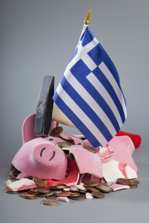 Broken piggy bank with Greek flag - symbolic image for the financial crisis of the European Union.. Stock Photo