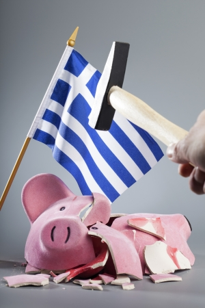 beroofd: Gebroken spaarvarken met Griekse vlag en een hand die een hamer - symbolisch beeld voor de dramatische financiële crisis van het land.
