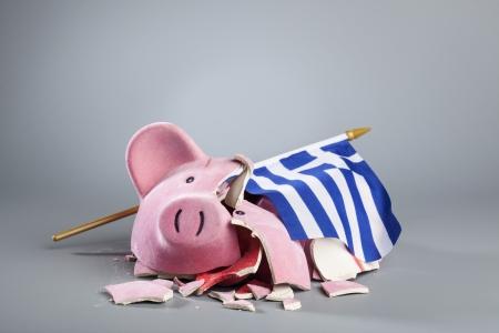 beroofd: Gebroken spaarvarken met Griekse vlag - symbolisch beeld voor de dramatische financiële crisis van het land. Stockfoto