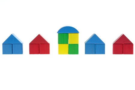Row of plain houses built with wooden toy blocks with one house in the middle being different than the rest.